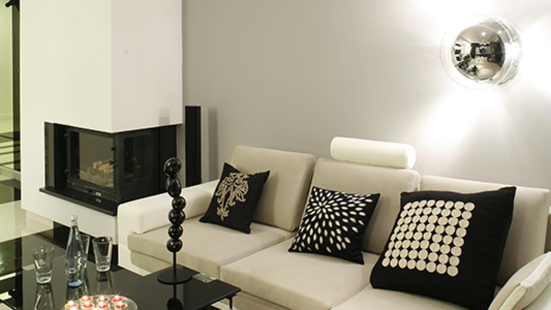 Strefę relaksu tworzą: modułowa kanapa Trivio (Bizzarto) w jasnym obiciu, z wygodnymi zagłówkami i funkcją spania, oraz stoliki kawowe z czarnego szkła i stali nierdzewnej (Moma Studio). Fot. Bartosz Jarosz.