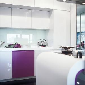 Kuchnia jest nowoczesna i minimalistyczna. Meble zostały wykonane na zamówienie według projektu architekt z mdf-u lakierowanego na wysoki połysk. Blaty robocze wykonano z corianu. Fot. Marta Znój.