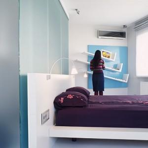 """Sypialnia jest równie nowoczesna i chłodna, jak reszta domu. Łóżko z CasaNova Collection tworzy całość z półkami ściennymi (proj. M. Czernik). Meble łączy wspólna kolor: biel. Półki tworzą zwariowaną konstrukcje, trzy """"przecinki"""" stanowią wyraźne pauzy na błękitnym tle. Fot. Marta Znój."""