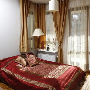 Niskie łóżko przykryto wspaniałą indyjską narzutą i poduszkami z tej samej, dekoracyjnej tkaniny. W oknach zawieszono złociste, połyskujące zasłony i zdobione lśniącymi cekinami. Fot. Bartosz Jarosz.