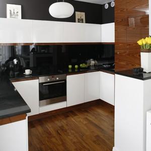 """Meble kuchenne wykonano z białego, lakierowanego MDF-u. Wszystkie szafki otwierają się bez pomocy tradycyjnych uchwytów, dzięki zachowaniu niewielkiej przestrzeni pod blatem. Smolisty połysk ścian to efekt zastosowania szkła """"Lacobel"""". Fot. Bartosz Jarosz."""