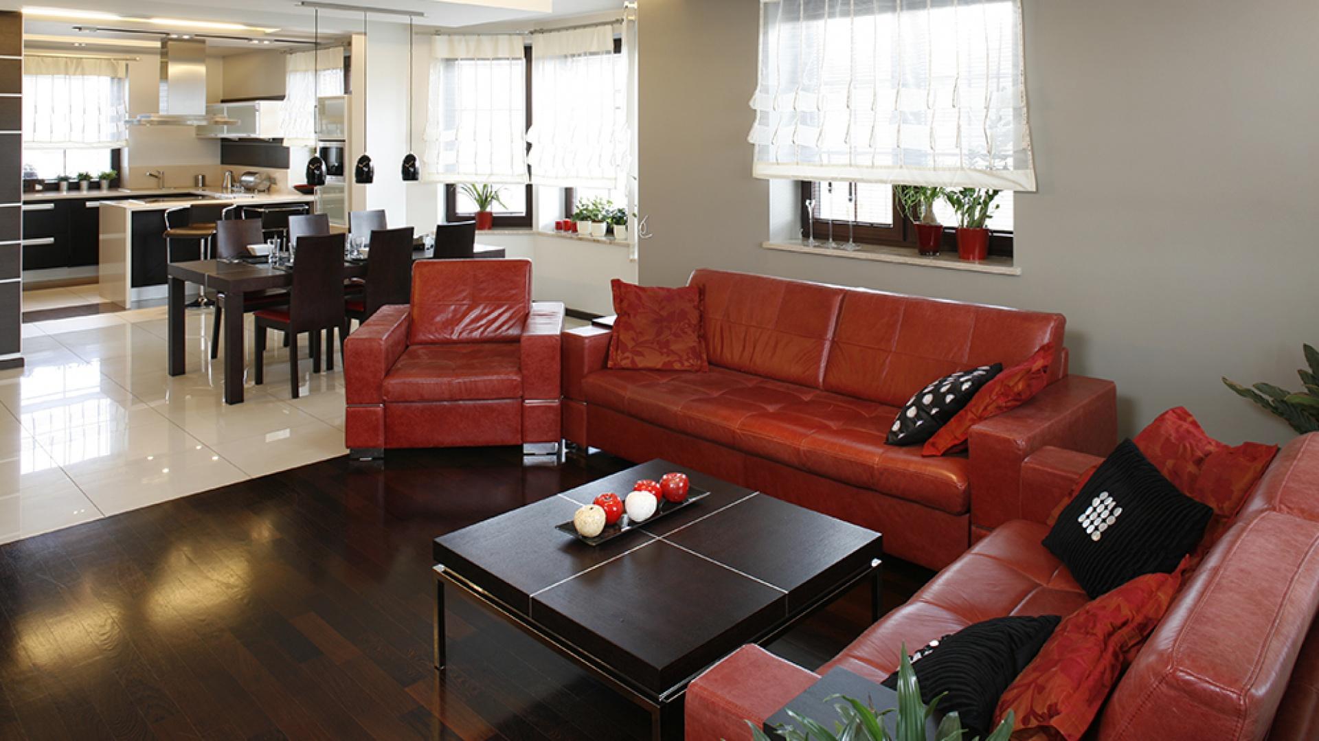 Stonowana baza kolorystyczna (brąz i beż) posłużyła jako tło dla mocniejszych w barwie akcentów – czerwony skórzany zestaw wypoczynkowy (Agata Meble) skutecznie ożywia wnętrze, podobnie jak nawiązujące do niego, czerwone obicia krzeseł jadalnianych (Paged). Fot. Bartosz Jarosz.