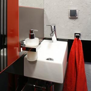 W toalecie gościnnej również pojawia się surowa, betonowa ściana. Złagodzona jest białą umywalką (Koło) oraz szlachetną, stalową armaturą i dodatkami. Fot. Bartosz Jarosz.