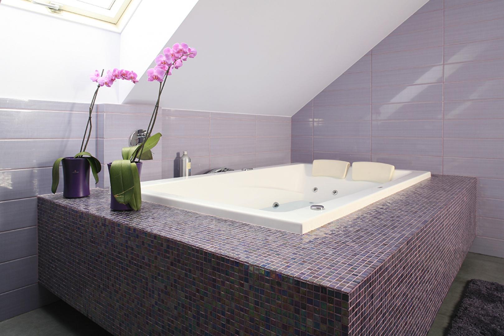 Duża łazienka na piętrze skąpana jest we fioletach. To oaza relaksu, co podkreśla dwuosobowa wanna z hydromasażem (Poolspa) obłożona mozaiką (Bisazza). Fot. Bartosz Jarosz.