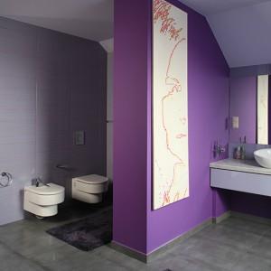 Gra kolorów wyznacza rytm tego wnętrza. Obecna jest pod postacią płytek: na podłodze szare (Novabell), na ścianach fioletowe (Cotto DST) jak i barw obrazu. Portret pani domu malowany fioletem i różem wyeksponowano na tle pomalowanej na fiolet ściany. Fot. Bartosz Jarosz.