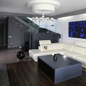 """Intrygującym tłem salonu jest ściana zdobiona ornamentem """"Tamaro"""" (Dohar) z materiału podobnego do pleksi o strukturze 3D. Jest ona godnym kontekstem dla współczesnej sztuki, jak i sporego wytwornego żyrandola (Voltolina, Amplex). Za wygodę odpowiada natomiast sofa w skórze (Selva). Fot. Bartosz Jarosz."""