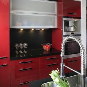 Meble kuchenne zostały wykonane na zamówienie z czerwonego mdf-u lakierowanego (lakierem samochodowym). Lekkości dodaje im szkło trawione, wprowadzone na frontach kilku szafek. Fot. Bartosz Jarosz.