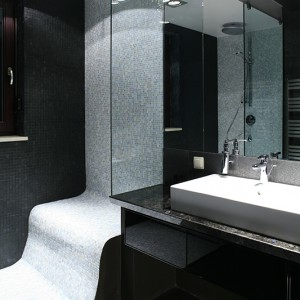 Perłowa mozaika (Bisazza) wygląda, jakby migotała. Zestawiona z czarnym łupkiem, w pełni eksponuje swoją urodę. Zaokrąglony narożnik w kabinie prysznicowej dodatkowo potęguje wrażenie pulsowania ściany. Fot. Bartosz Jarosz.