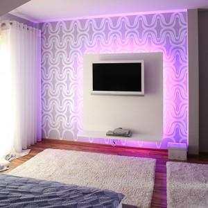 Sypialnia jest subtelna, skąpana w bielach i ocieplona drewnianą podłogą. Jednak w sekundę można odmienić tu klimat. Ściana za panelem z TV jest pokryta ornamentem proj. Dominika Respondka i dodatkowo podświetlona RGB. Wrażenia op-art gwarantowane i to w kilku różnych kolorach. Fot. Bartosz Jarosz.