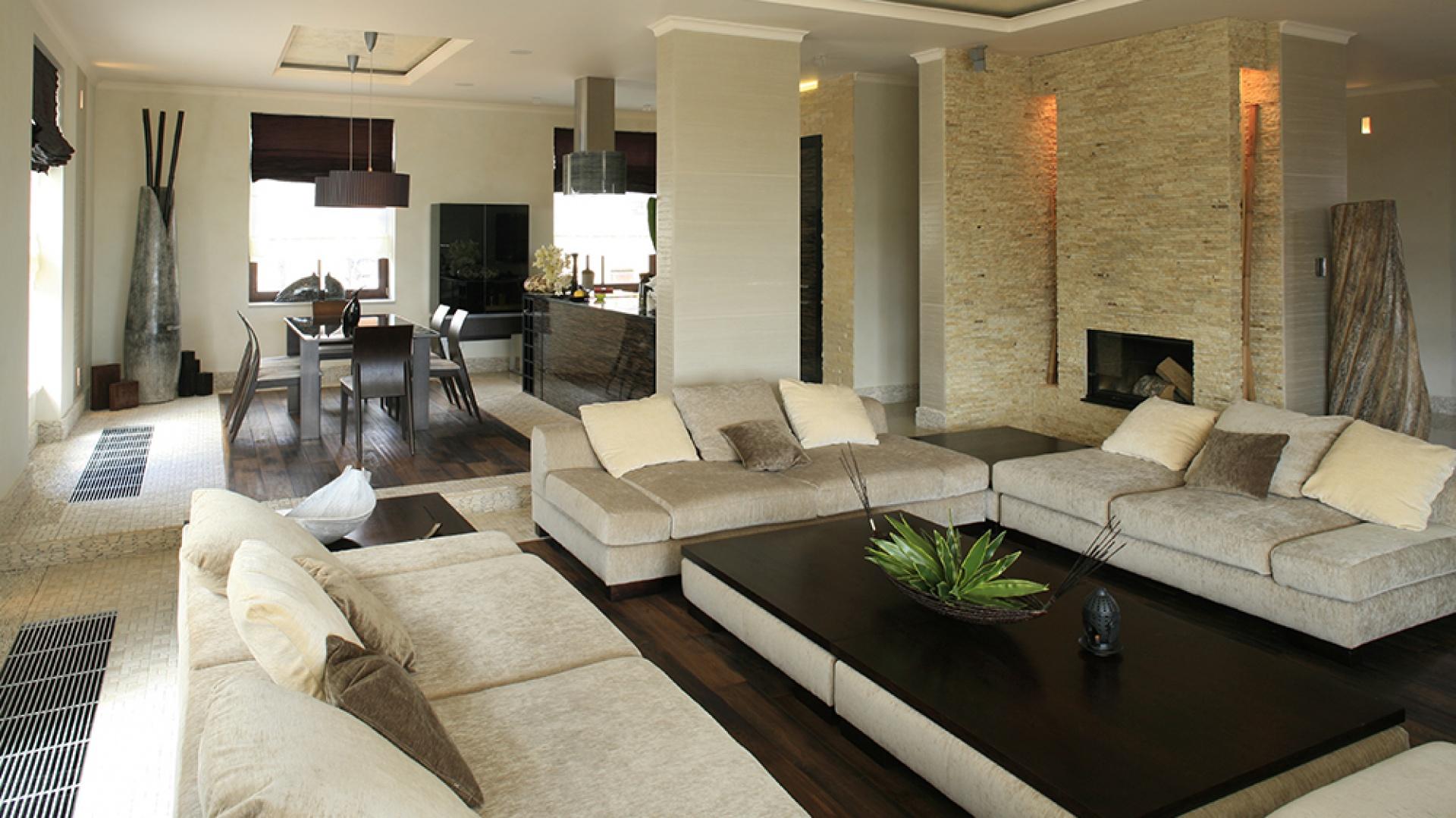 Przyjazny klimat wnętrza to w dużej mierze zasługa użytych materiałów: okazały kominek został obłożony drobnym łupkiem piaskowca, zaś podłogę wyłożono częściowo postarzanym litym drewnem egzotycznym (Komfort), a częściowo – indonezyjską, marmurową mozaiką. Fot. Bartosz Jarosz.