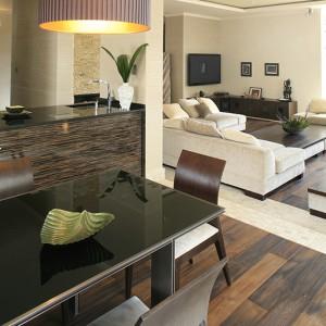 Stół z blatem z czarnego szkła, zdobionym delikatnym motywem kwiatowym, zestawiono z zestawem jasnych krzeseł. Całość pochodzi z oferty Venotti. Fot. Bartosz Jarosz.