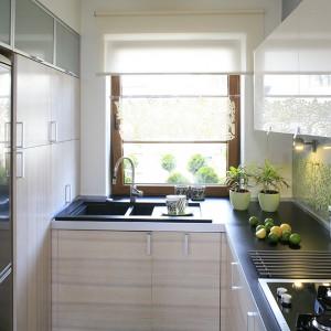 Strefa robocza w kształcie litery L organizuje niewielką przestrzeń kuchni. Na jednej ścianie stworzono miejsce na głębokie szafki i lodówkę. Zabudowa kuchenna została wykonana na zamówienie. Fot. Bartosz Jarosz.