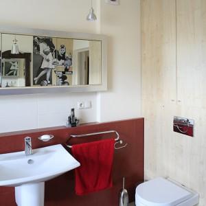 Zabudowa podtynkowego stelaża spłuczki została wykończona drewnianą sklejką, a wnęka powyżej zamknięta frontami szafki łazienkowej z tego samego materiału. Fot. Bartosz Jarosz.