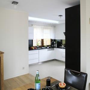 W kuchni dominują białe fronty mebli kuchennych – wykończone na wysoki połysk, ukrywają m.in. zmywarkę Bosch. Duże okno idealnie doświetla roboczą strefę blatu. Fot. Bartosz Jarosz.