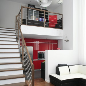 Przestrzeń dzienną tworzy salon skąpany w delikatnych beżach, gabinet na antresoli oraz najgorętszy akcent – czerwona kuchnia. Fot. Bartosz Jarosz.