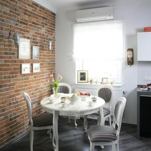 Komplet stylowych krzeseł oraz stołu w jadalni łagodzi loftową surowość. Ściana wykonana ze sprowadzonych ze Śląska cegieł rozbiórkowych; na jej tle umieszczono łódzkie grafiki – z rodzinnego miasta właścicielki mieszkania. Fot. Bartosz Jarosz.