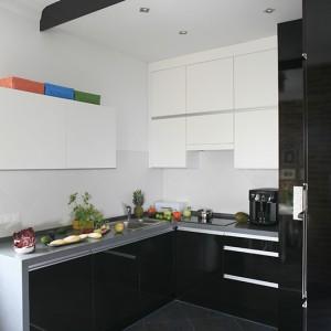 Zabudowa kuchenna to połączenie białych i czarnych frontów lakierowanych na wysoki połysk. Nad całością umieszczono podwieszany sufit i industrialne oświetlenie marki Massive. Fot. Bartosz Jarosz.