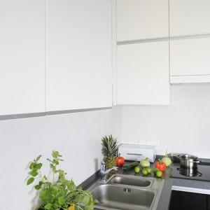 Po lewej – dwie szafki wiszące, po prawej – dwa rzędy szafek górnych umieszczonych pod sufitem. Na ścianie nad blatem płytki ceramiczne ułożone w karo dodają nieco charakteru retro. Fot. Bartosz Jarosz.