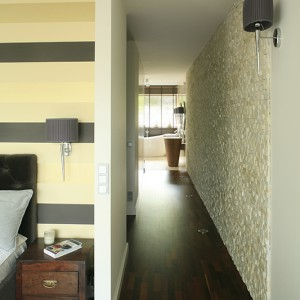 """Łazienka nie jest zamykana drzwiami, za to połączona  z sypialnią pani i pana domu korytarzem;  ścianę w przejściu wykończono łupkiem (Kimar  Pro Art """"Guam""""). Oba pomieszczenia tworzą komfortowy apartament z osobną garderobą (wejście z korytarza). Fot. Bartosz Jarosz."""