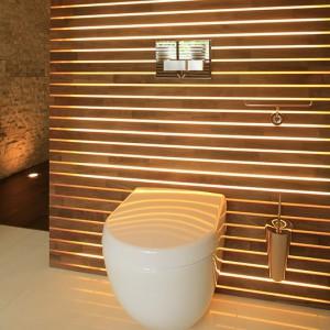 """Okładzina ściany za sedesem (""""Subway"""" Villeroy&Boch, spłuczka Geberit z przyciskiem """"Sigma 50"""") to połączenie pleksi oraz drewna tekowego, za  którymi znajdują się świetlówki. Daje to efekt dekoracyjnego podświetlenia. Fot. Bartosz Jarosz."""