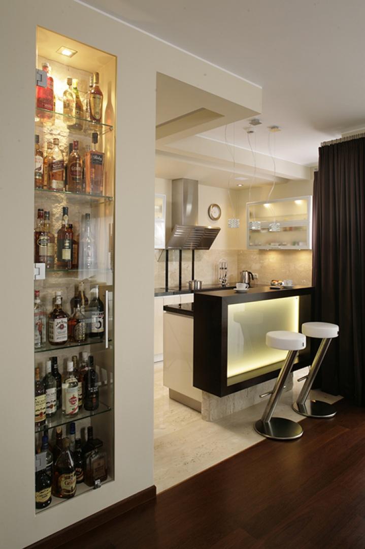 Na granicy kuchni i jadalni znajduje się efektowny barek. Niewielka wnęka w ścianie została wyposażona w szklane półeczki, podświetlona oraz przysłonięta wysokim, szklanym frontem. Fot. Bartosz Jarosz.