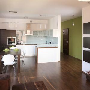 Kuchnia oraz salon tworzą spójną przestrzeń dzienną, co podkreśla jednolita podłoga z desek (dąb kolonialny). Fot. Bartosz Jarosz.