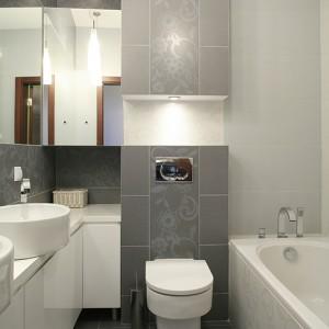 """Głównym elementem dekoracyjnym łazienki są płytki ceramiczne z motywem kwiatowym (kolekcja """"Amanda"""" Ceramiki Paradyż). Oświetlona wnęka nad przyciskiem spłukiwania dodaje przestrzeni, a efekt głębi dodatkowo podkreśla zastosowanie białych płytek, przełamujących szarość. Fot. Bartosz Jarosz."""