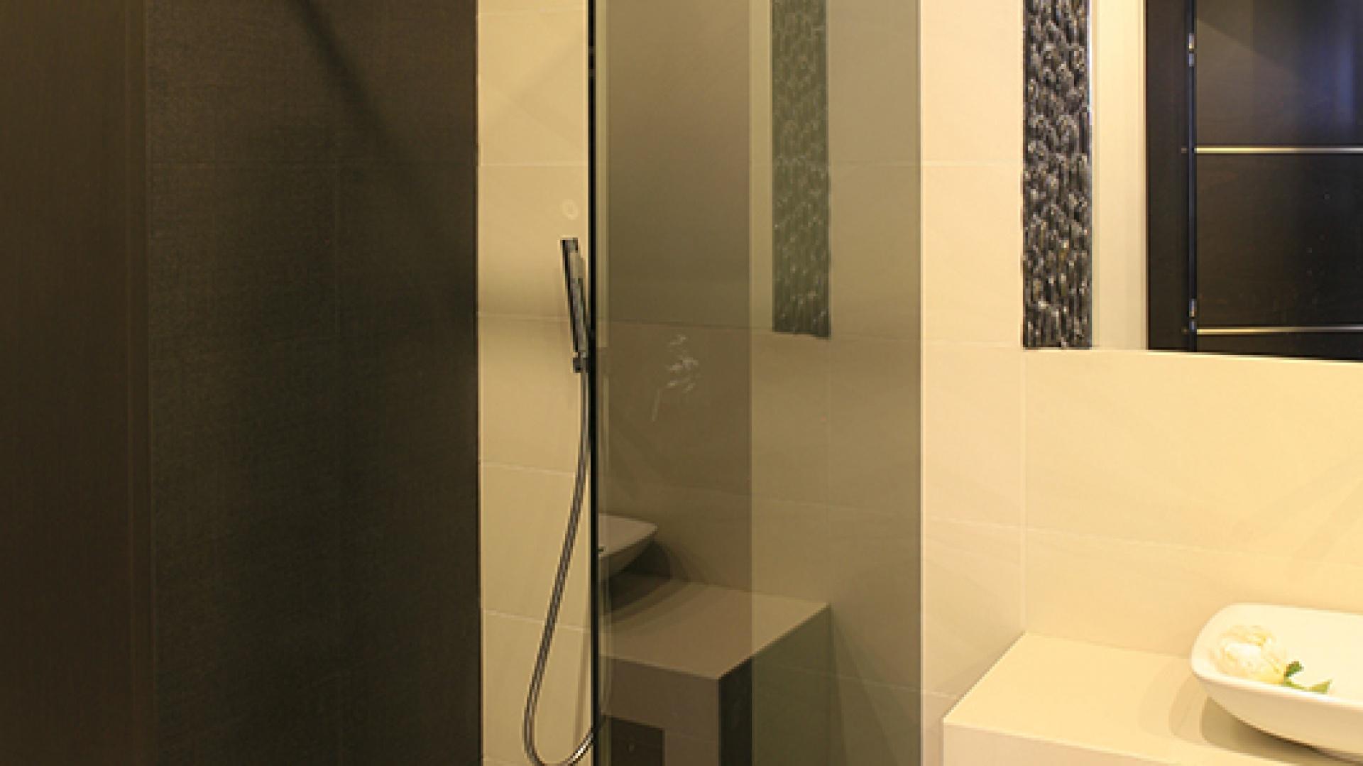 """Tafla grafitowego, a więc mniej przeziernego szkła, oraz wykończona czarnymi płytkami ceramicznymi ściana wyznaczają strefę kabiny prysznicowej typu walk-in z odpływem w posadzce. Bateria prysznicowa marki Tres z serii """"Max-Tres"""", deszczownica """"Cascada Maxi"""" Deante. Fot. Bartosz Jarosz."""