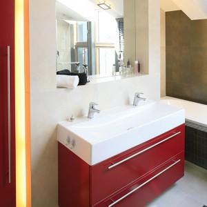 """Czerwone meble z MDF-u zostały zaprojektowane specjalnie do tego wnętrza. Na podwieszanej komodzie prostokątna umywalka marki Koło z parą baterii """"Jaguar Line"""" firmy Deante. Fot. Bartosz Jarosz."""