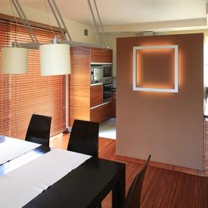 """Zabudowa kuchenna częściowo wkracza do jadalni. Obie strefy delikatnie oddziela ściana z płyty gipsowo-kartonowej, o niepełnej wysokości, pomalowana na kolor brązowy. Na ścianie – kinkiet """"Open Grill Wall"""" marki Spotline, którego światło odbija się od ściany. Fot. Bartosz Jarosz."""