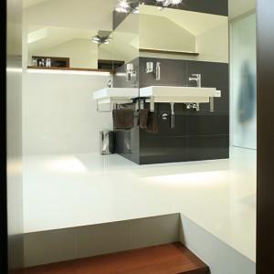 """Miejsce na kabinę prysznicową wyznaczyła architektura pomieszczenia. Wnęka powstała w najwyższej części łazienki. Na ścianach, po zewnętrznej stronie, umieszczone zostały umywalki (Catalano """"Verso""""), do których dobrano baterie umywalkowe """"Metris S"""" firmy Hansgrohe. Fot. Bartosz Jarosz."""