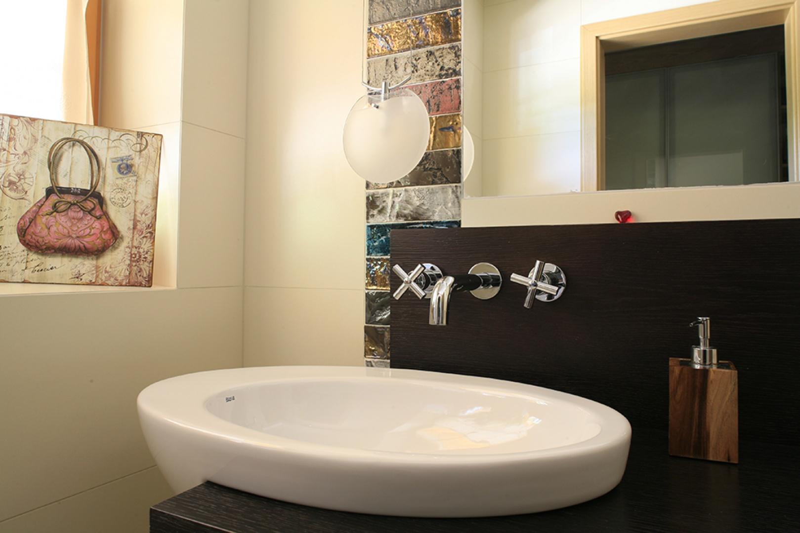 """Umywalka wraz ze ścianką w kolorze wenge pochodzą z kolekcji """"Eliptic"""" marki Roca. Nowoczesny design i ciepłe drewno – to klucz do wystroju tej toalety. Fot. Bartosz Jarosz."""