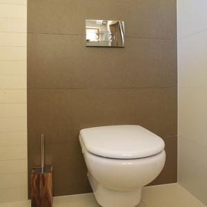 W toalecie zastosowano płytki w odcieniach kremu i orzecha (Porcelanosa), które nawiązują kolorystycznie do drewna, mocno obecnego w domu w stylu zakopiańskim. Fot. Bartosz Jarosz.