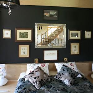 Łóżko zostało wykonane na zamówienie, według projektu. Jego oryginalna, drewniana rama, otaczająca całą ścianę, stała się przy okazji swoistą ramą dla małej galerii sztuki. Fot. Bartosz Jarosz.