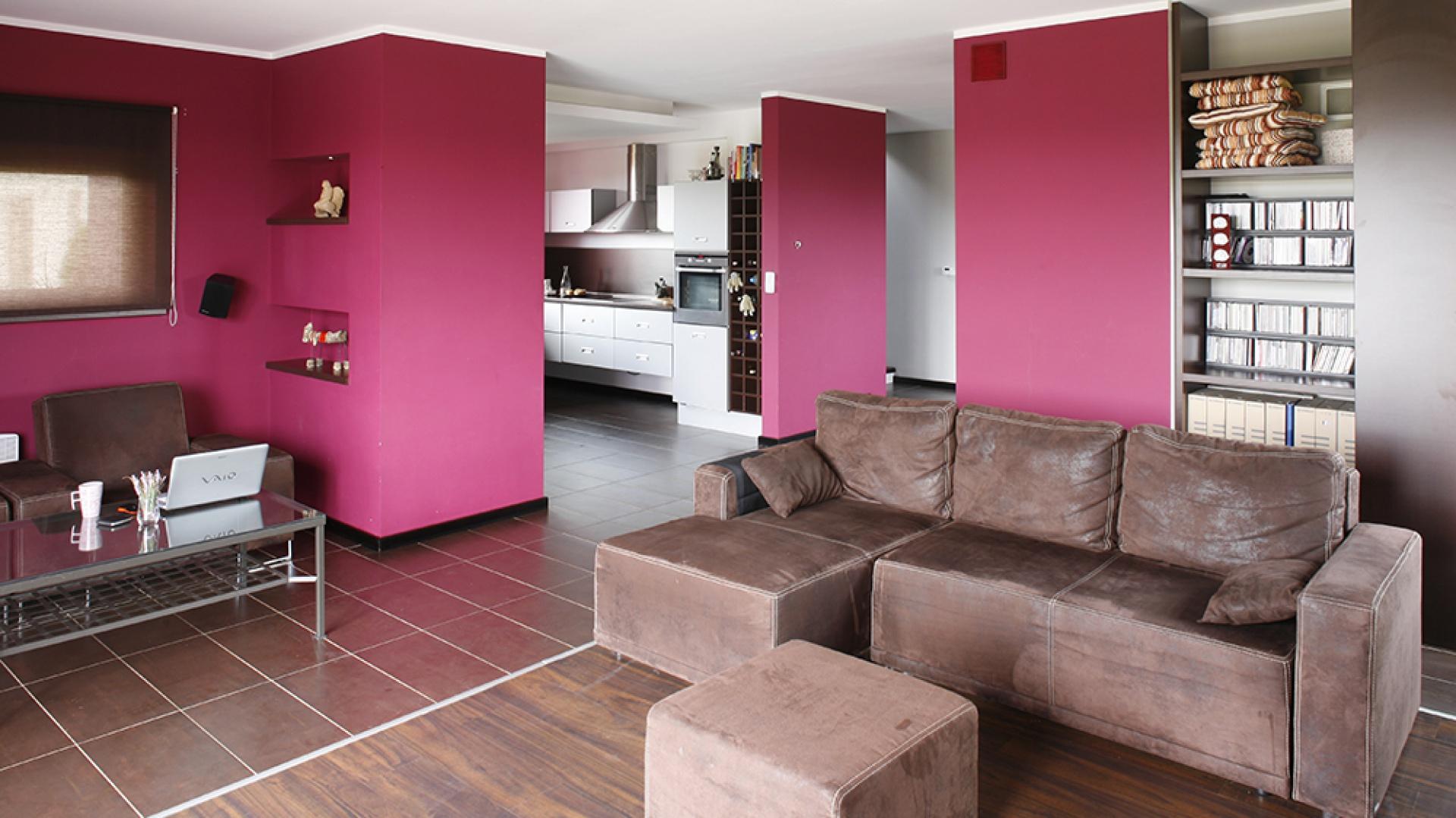 Głównym elementem wyposażenia jest ciemnobrązowy komplet kanap (Presmebel), rozmieszczonych w strategicznych miejscach.  Zamiast typowych szafek i regałów, wprowadzono schowki i półki, wbudowane w pomalowane na purpurowo ściany. Fot. Bartosz Jarosz.