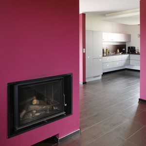 Wbudowany w ścianę kominek (Jøtul) swą prostą, lecz stylową formą i nowoczesnym designem podkreśla ideę przewodnią aranżacji całego wnętrza – funkcjonalność i minimalizm. Fot. Bartosz Jarosz.