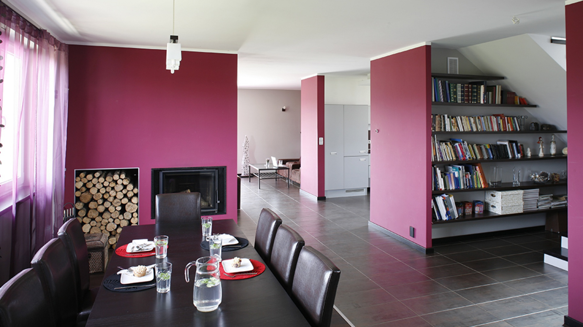 W okazałej strefie jadalnianej stanął długi stół (IKEA) i tuzin krzeseł (Allegro). Familijny charakter tego miejsca podkreśla wkomponowany w purpurową ścianę, minimalistyczny kominek oraz duży, otwarty schowek na drzewo. Fot. Bartosz Jarosz.