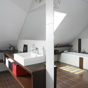 Prostokątna umywalka wmontowana jest w podwieszane szafki o niestandardowej wysokości (ponad 80 cm). Wrażenie mnogości przestrzeni stwarzają zamontowane w całej łazience surowe lustra. Fot. Bartosz Jarosz.