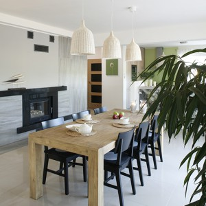 Duża i wygodna jadalnia została umieszczona pomiędzy salonem a kuchnią, na przeciwko przestronnych okien, przez które – podczas rodzinnych posiłków – można podziwiać las. Fot. Bartosz Jarosz.