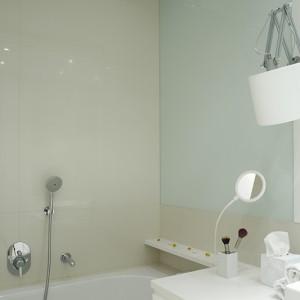 Duże lustra oraz szklane tafle przyklejone do ścian (ściana nad wanną), tworzą iluzję zwiększonej przestrzeni … A nad wszystkim czuwa ponadczasowa biel. Fot. Bartosz Jarosz.