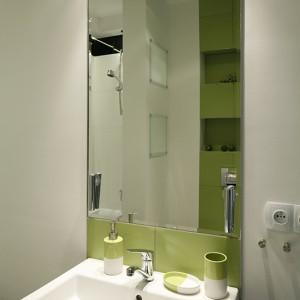 Oś sanitariatów akcentuje pas jasnozielonych płytek; pod kolor okładzin dobrano również akcesoria łazienkowe. Ceramika sanitarna została wybrana z oferty Koło. Fot. Bartosz Jarosz.