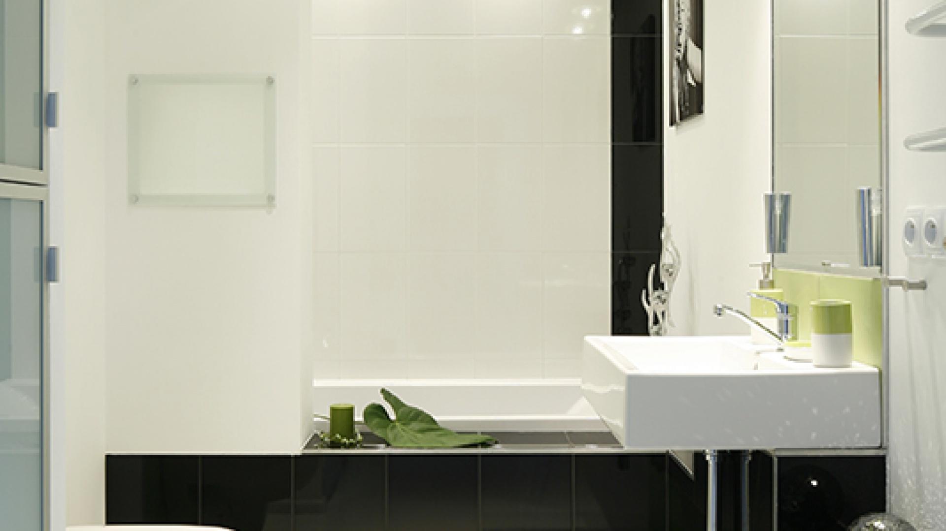 Przesłona wanny (Cersanit) to forma nowoczesnego parawanu, z półkami osłoniętymi szkłem. Pralka schowana dyskretnie w zabudowanym słupku (po lewej) nie zdradza swej obecności. Fot. Bartosz Jarosz.