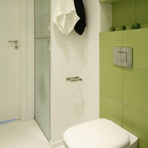 W dużej szafie łazienkowej ukryta została pralka, ponad nią zamontowano praktyczne póki na detergenty; fronty z mlecznego szkła w aluminiowych ramkach. Podwieszany sedes z oferty Koło, spłuczka - Grohe. Fot. Bartosz Jarosz.