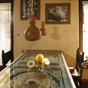 Piękny, intarsjowany stół kupiony został w warszawskim sklepie z indyjskimi przedmiotami Guido. Na ścianie – portrety ulubieńca właścicieli. Fot. Bartosz Jarosz.