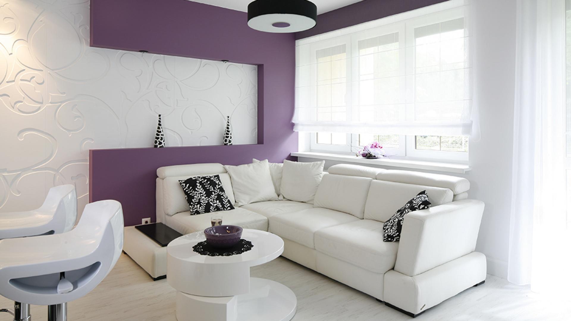W salonie dominuje duża narożna kanapa wykonana ze skóry naturalnej (Play, Gala Meble). Wprowadzony w postaci gipsowej ścianki o zabawnym, geometrycznym kształcie wrzos stanowi dla niej mocno zaakcentowane, ożywcze tło. Fot. Bartosz Jarosz.