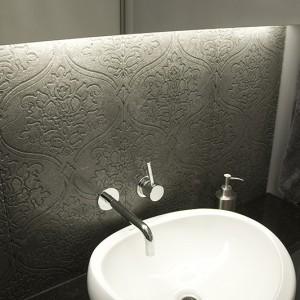 Znajdująca się na parterze malutka łazienka gościnna musiała być równie efektowna, jak reszta parteru. Czarny blat granitowy wycięty w miękki kształt podkreśla formę umywalki. Nad nim dekoracyjne płytki gresowe z wyszukanym ornamentem. Fot. Małgorzata Opala.