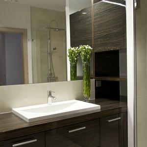 Łazienka gościnna na piętrze została utrzymana w ciepłej tonacji. Płytki w kolorze beżowego trawertynu stanowią idealne tło dla szklanej zabudowy prysznica oraz eleganckich i pojemnych mebeli i półeczek. Fot. Małgorzata Opala.