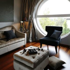 Ulubiony pokój pani domu, elegancki i wysmakowany pod względem doboru mebli, tkanin obiciowych. Do tego stalowe zasłony podkreślające obowiązujący tu, okrągły kształt okna. Fot. Marcin Onufryjuk.