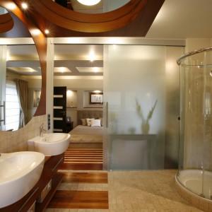 Transparentna szklana przegroda optycznie łączy sypialnię i łazienkę, a podłogowe inkrustacje dodatkowo potęgują przenikanie się tych przestrzeni. Fot. Marcin Onufryjuk.