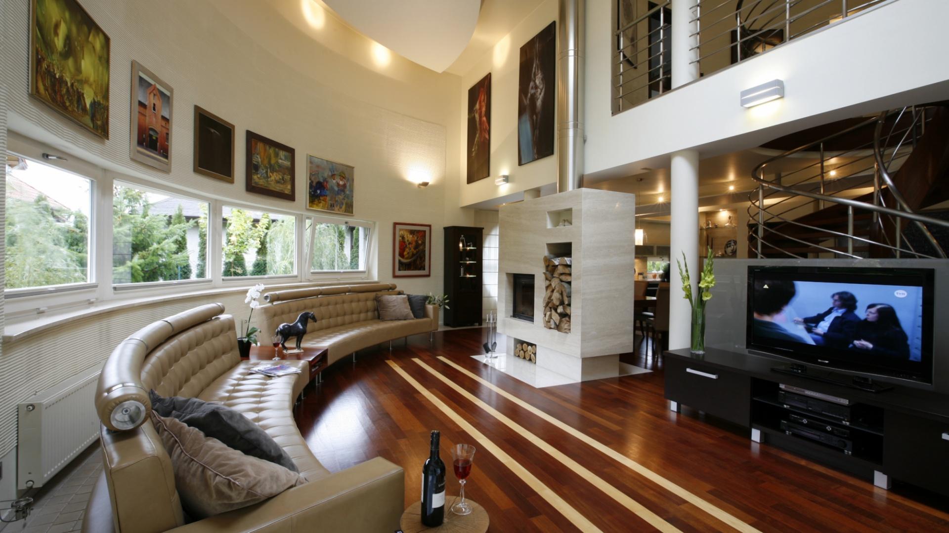 Niekonwencjonalne rozwiązanie łukowej ściany nadaje ekspresji salonowej dwukondygnacyjnej części domu, dla przeciwwagi dwustronny kominek, zaprojektowany przez łódzkich architektów, powstał na bazie czystych, prostych brył. Fot. Marcin Onufryjuk.